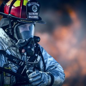 Close up of firefighter with fire in background