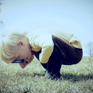 curious child looking through magnifying glass