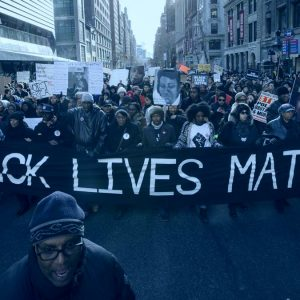 black white matters protester with BLM banner